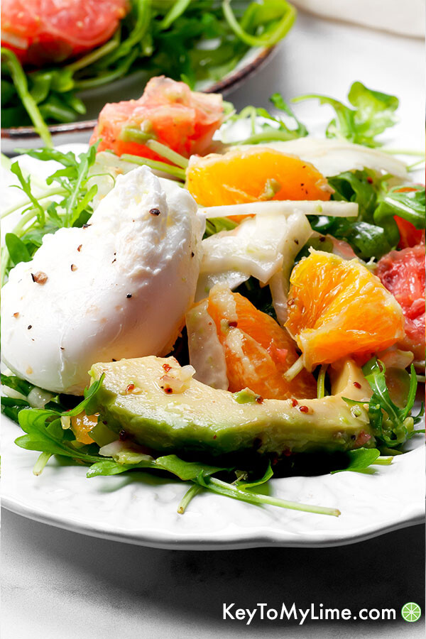 A close up side image of salad on a white plate with a poached egg.