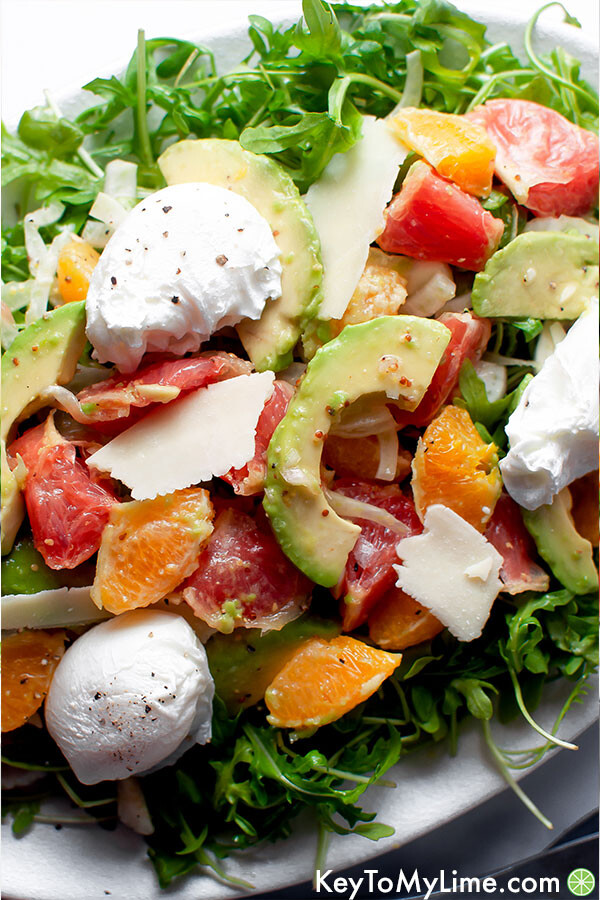 An overhead image of salad on a white oval platter.