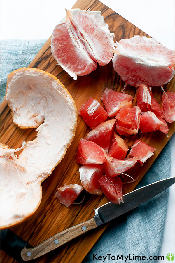 A wood cutting board with a grapefruit peel and grapefruit wedges being cut into chunks.