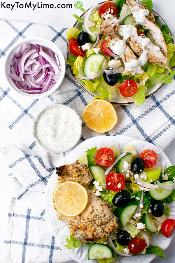 Two plates of Greek chicken salad with containers of sliced red onion, lemon slices, and lemon dill dressing.