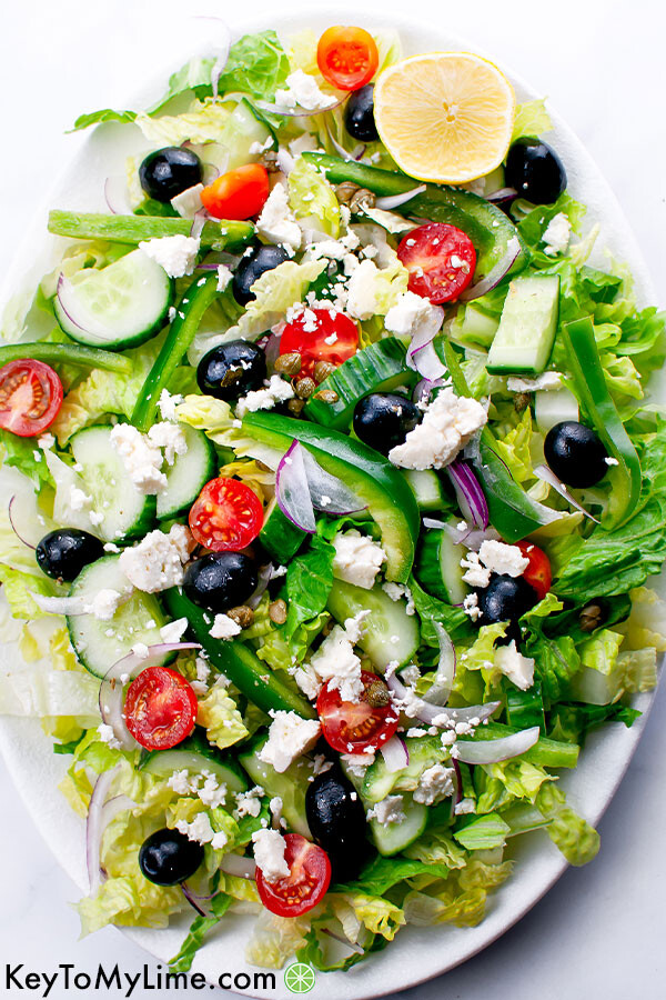An overhead image of Greek salad on a white oval platter.