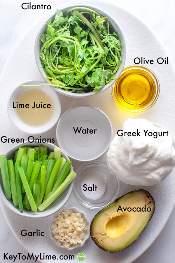 Cilantro lime dressing ingredients in individual containers and labeled (ingredients include cilantro, olive oil, Greek yogurt, avocado, salt, garlic, green onion, lime juice, and water).
