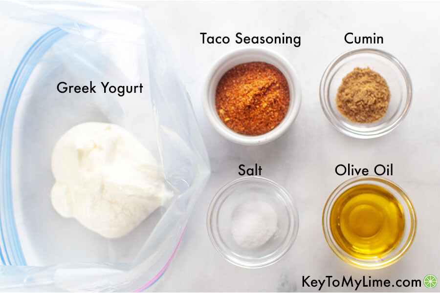 Southwest chicken marinade ingredients in individual containers and labeled (ingredients include Greek yogurt, taco seasoning, cumin, salt, and olive oil).