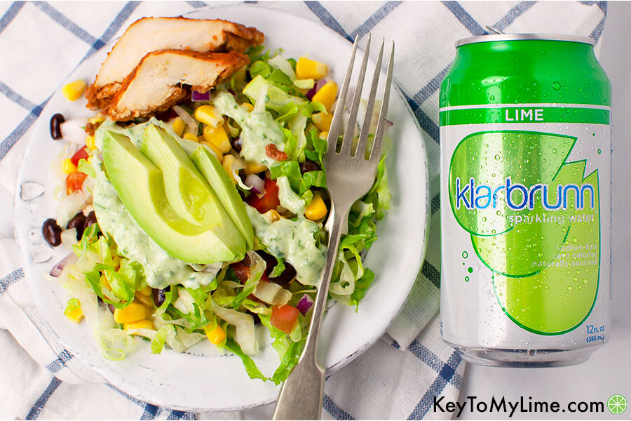 Southwest chicken salad on a white plate with a silver fork next to a can of Klarbrunn sparkling water.