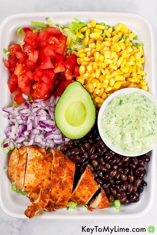 An image of of southwest chicken salad on a white platter with the ingredients segmented.