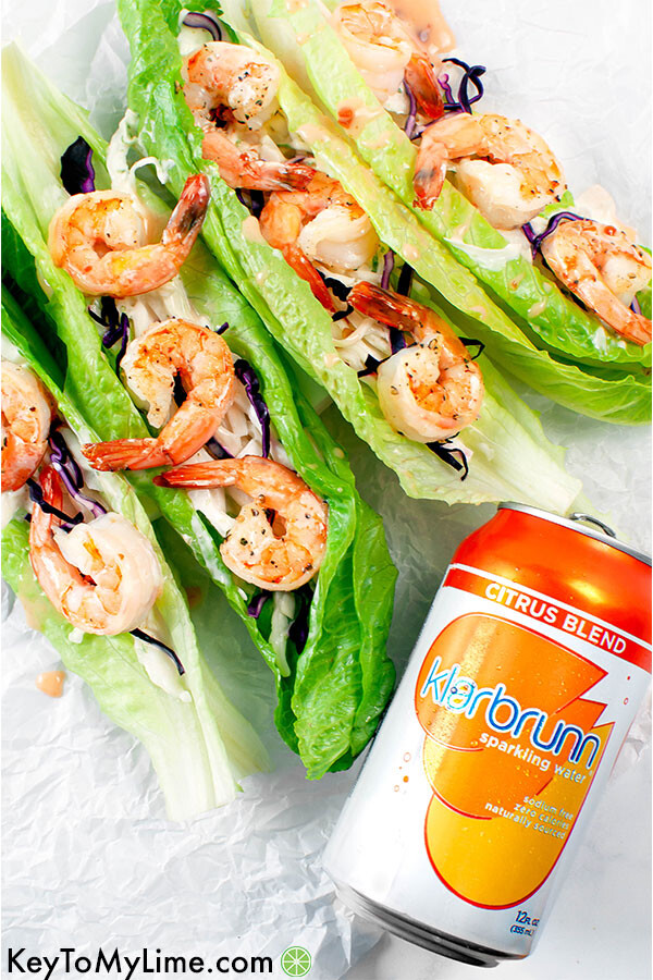 Four shrimp lettuce cups with a can or Klarbrunn sparkling water.