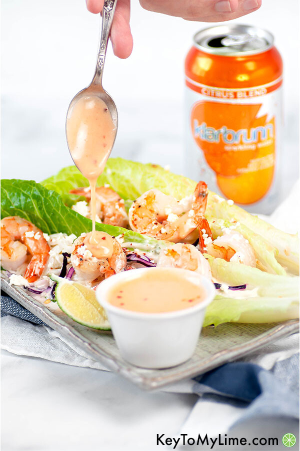 Bang bang sauce dripping off of a spoon onto shrimp lettuce cups.