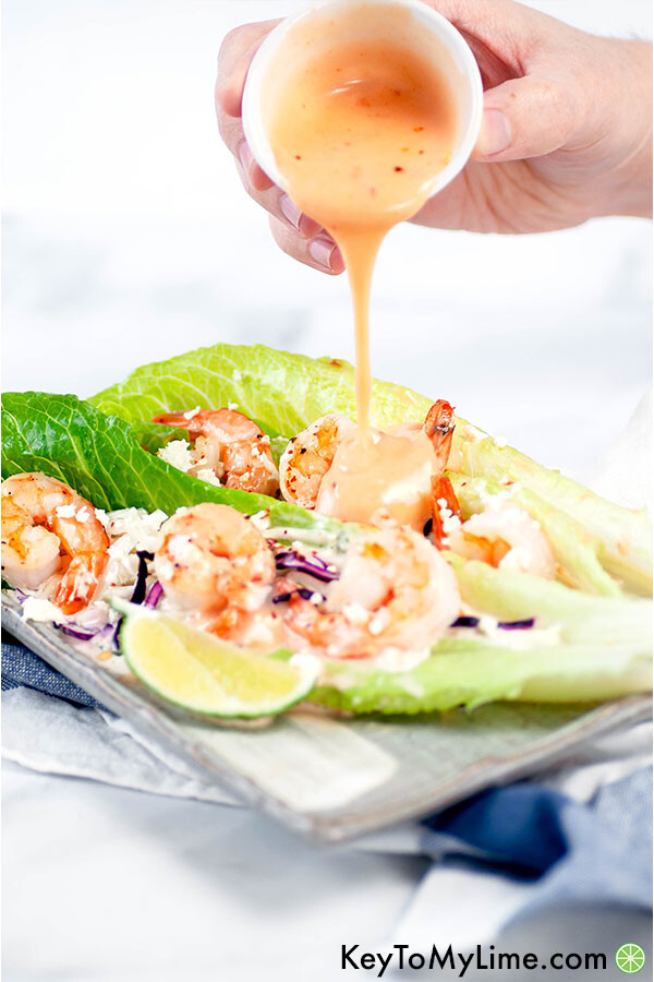 A hand pouring bang bang sauce on shrimp lettuce cups.