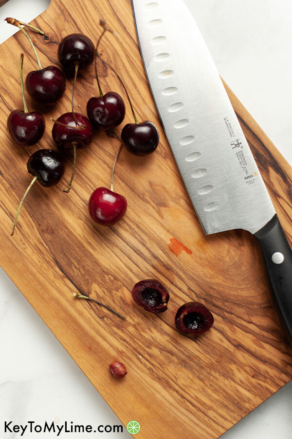 A wood cutting board with cherries and a knife.