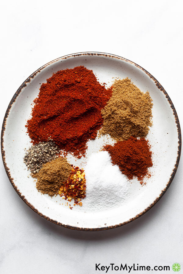Chicken taco seasoning ingredients separated on a white plate with a white background.