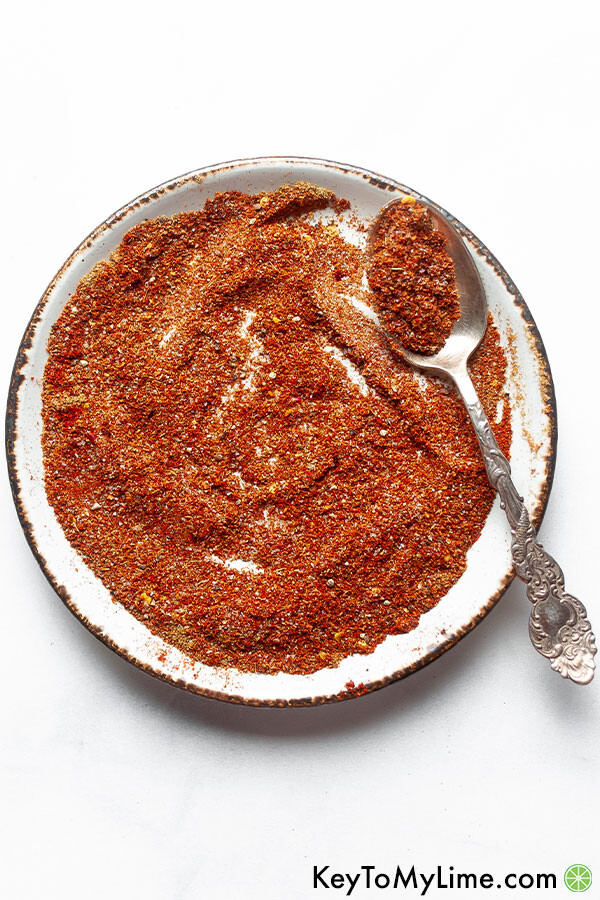 Taco seasoning mixed together on a light plate with an ornate silver spoon.