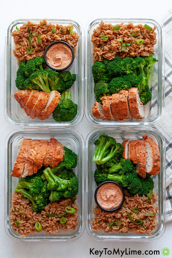 Four containers of chicken, rice, and broccoli meal prep on a white background.