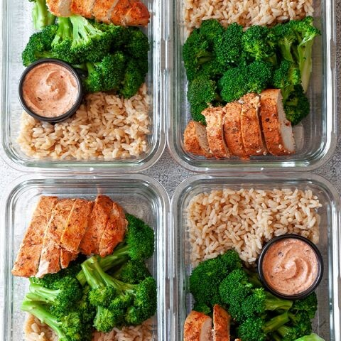 Four meal prep containers with chicken, rice, and broccoli.