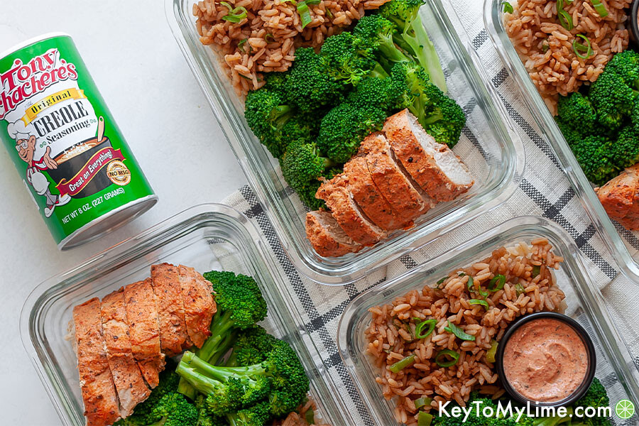 Glass meal prep containers next to a bottle of the cajun seasoning used to flavor the chicken.