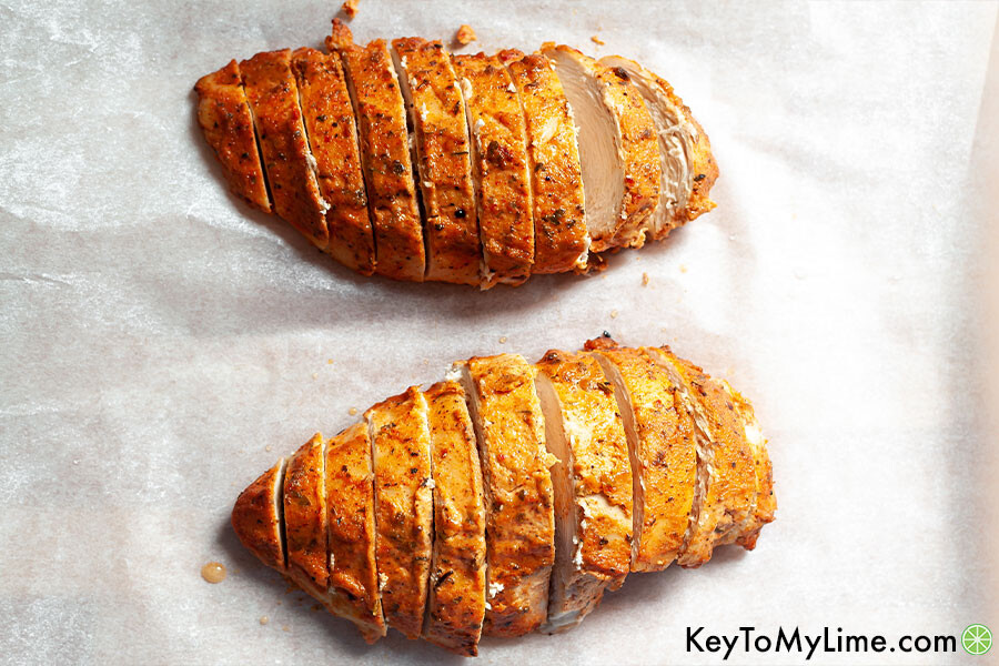 Two baked cajun flavored chicken breasts cut into slices.