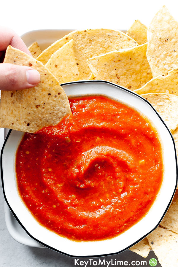 A hand dipping a chip in a bowl of restaurant style salsa.