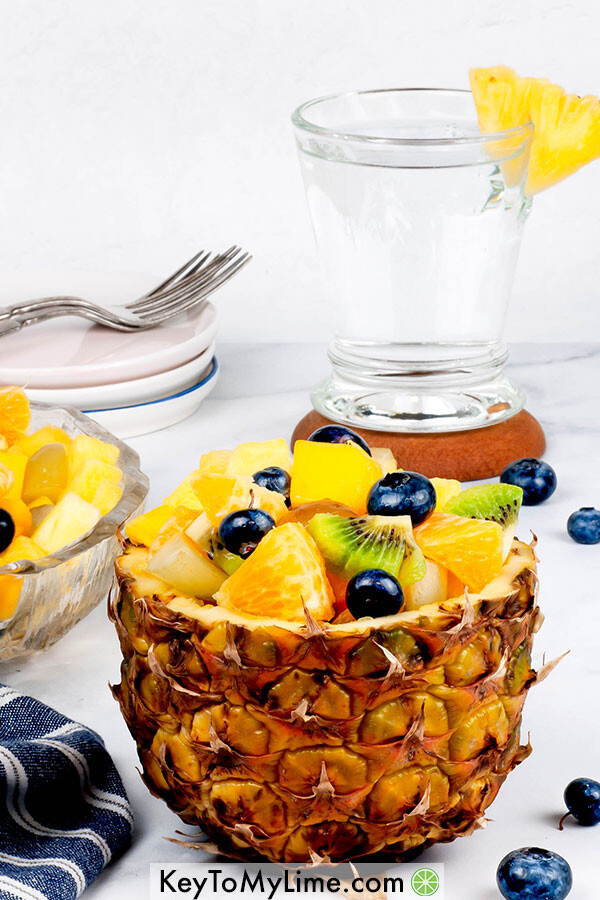 A side image of tropical fruit salad in a pineapple boat with a glass of water in the background.