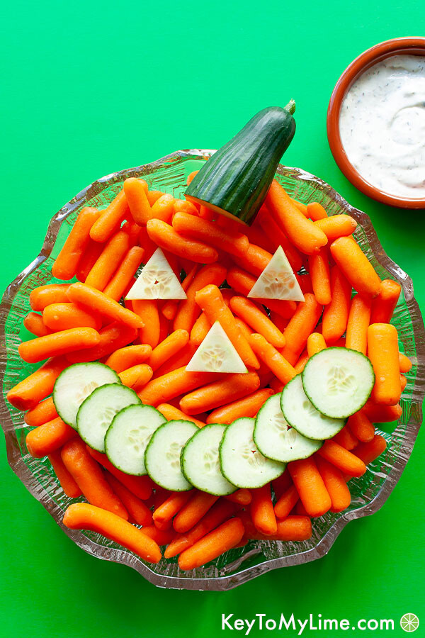 A Jack-o'-Lantern veggie tray made with carrots and cucumber slices.