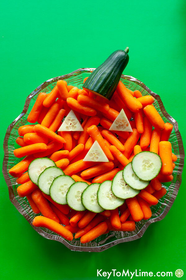 A close up image of the Jack-o'-Lantern made out of carrots and cucumber slices.