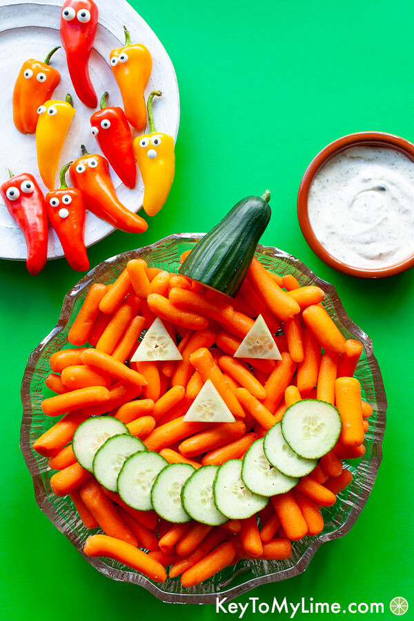 A halloween vegetable tray with a carrot Jack-o'-Lantern, sweet pepper ghosts, and dipping sauce.