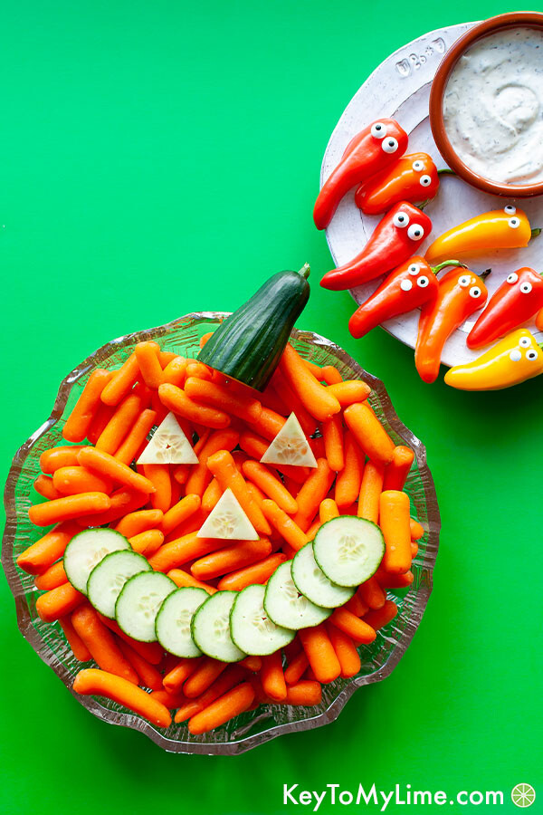 A Halloween themed vegetable tray with a carrot pumpkin and sweet pepper ghosts.