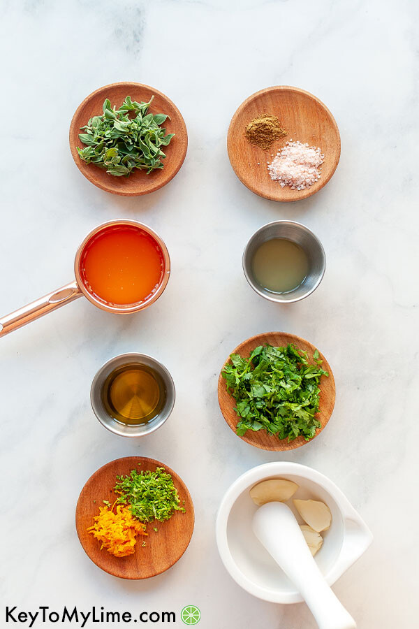 An image showing the ingredients for mojo marinade laid out in small containers.