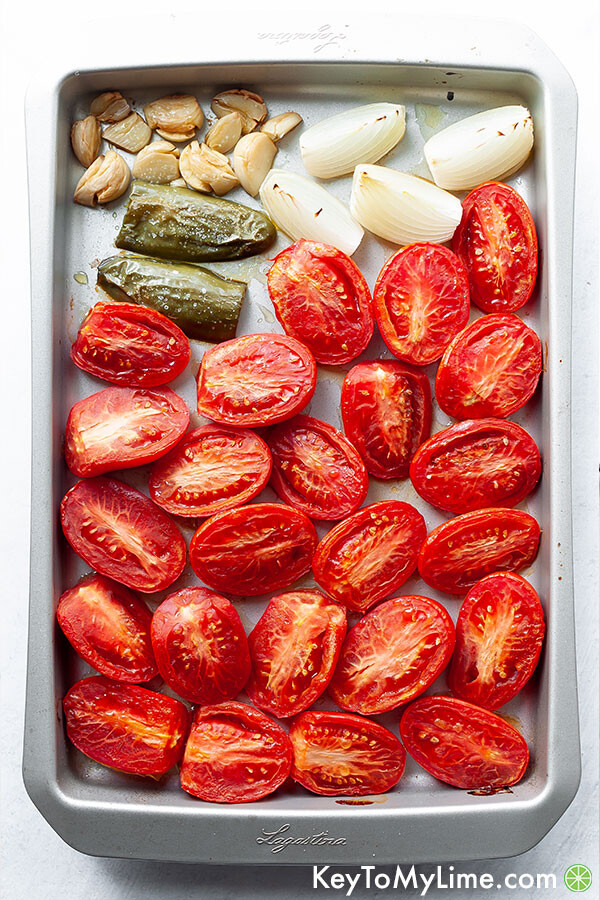 Tomatoes, jalapeno, onion, and garlic on a baking sheet after cooking.