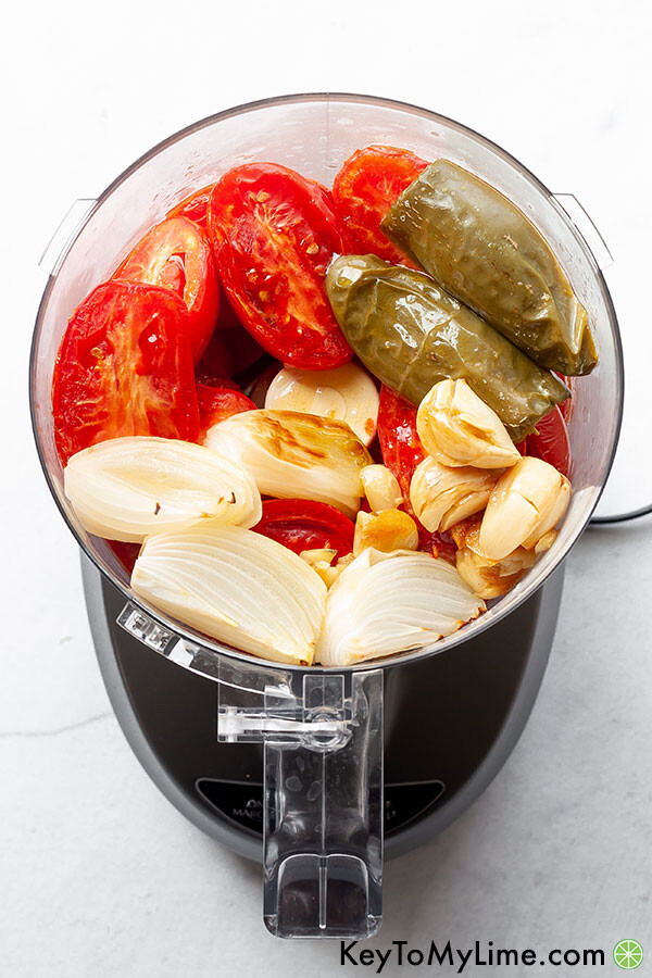Cooked tomatoes, jalapeno, garlic, and onion in a food processor.