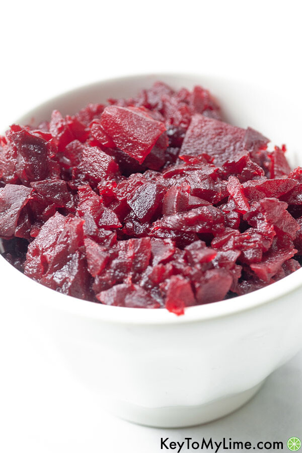 Roasted and diced beet in a small white bowl.