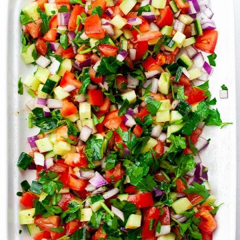 An overhead image of tomato cucumber salad in a white platter.