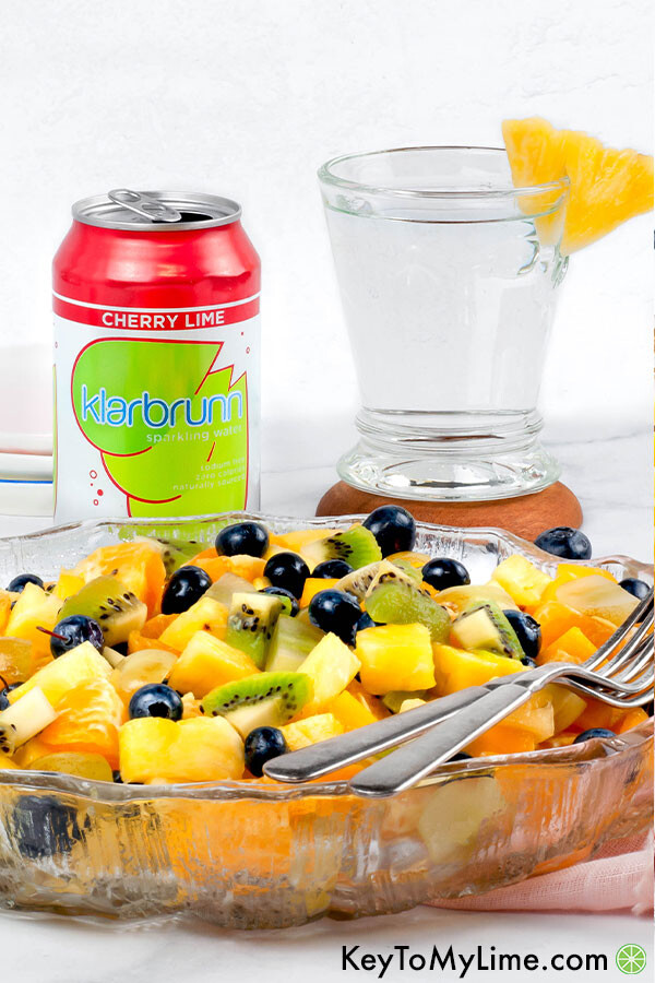 A side image of pineapple fruit salad with a can and a glass of Klarbrunn sparkling water in the background.