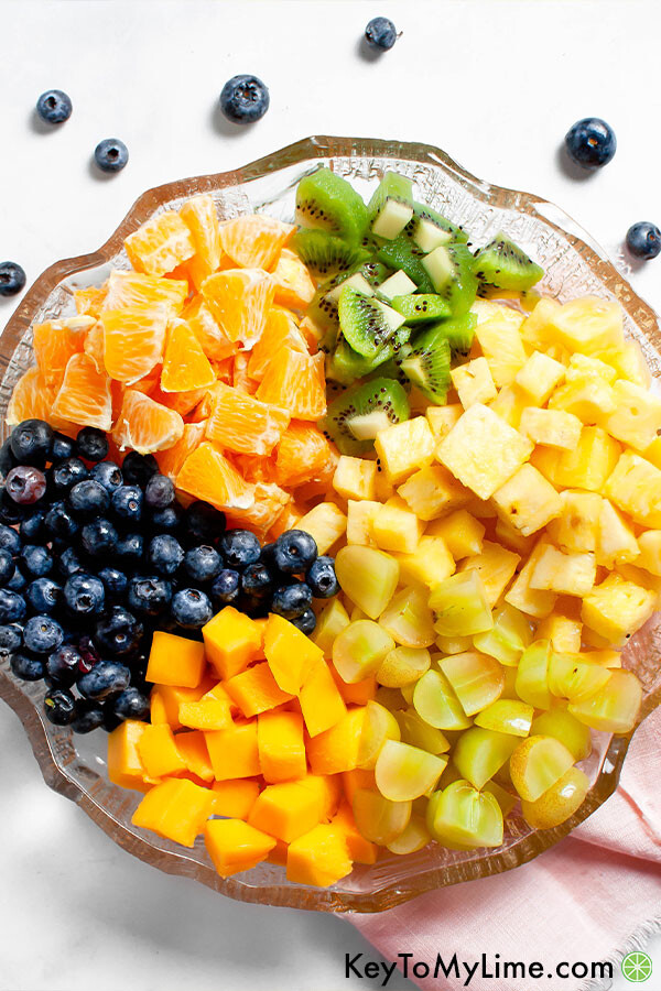 The ingredients for tropical fruit salad places separately in a large glass bowl.