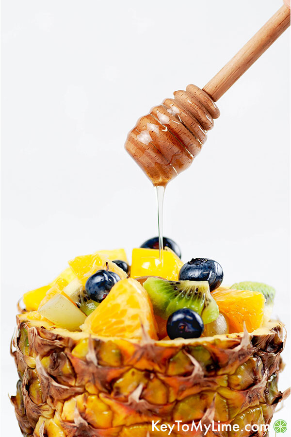 Tropical fruit salad in a pineapple boat with a honey wand drizzling honey dressing on top.