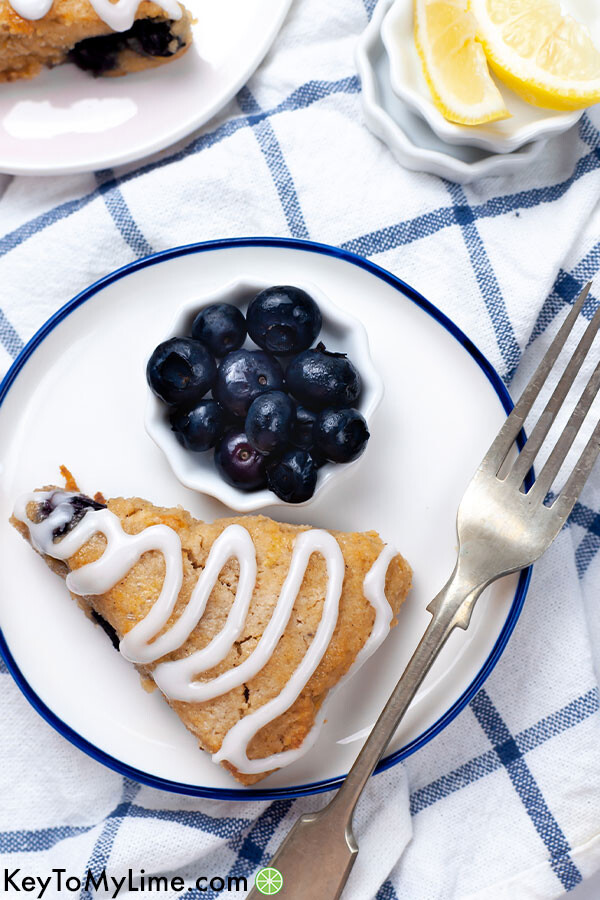 A keto scone on a plate with blueberries and a fork.