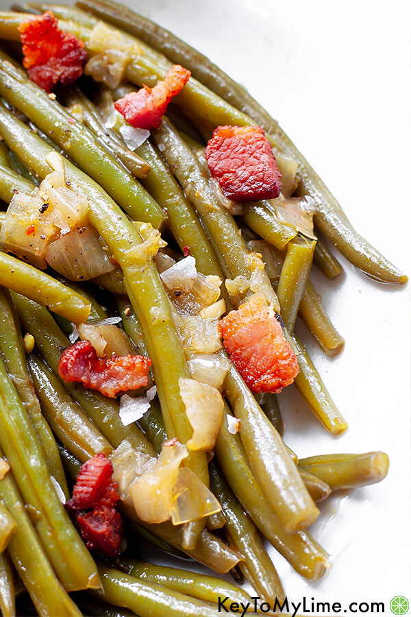 A close up image of green beans with bacon.