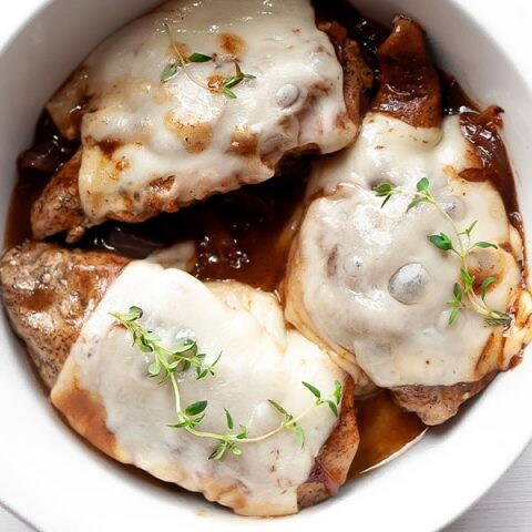 Three French onion chicken breasts in a white circle baking dish.