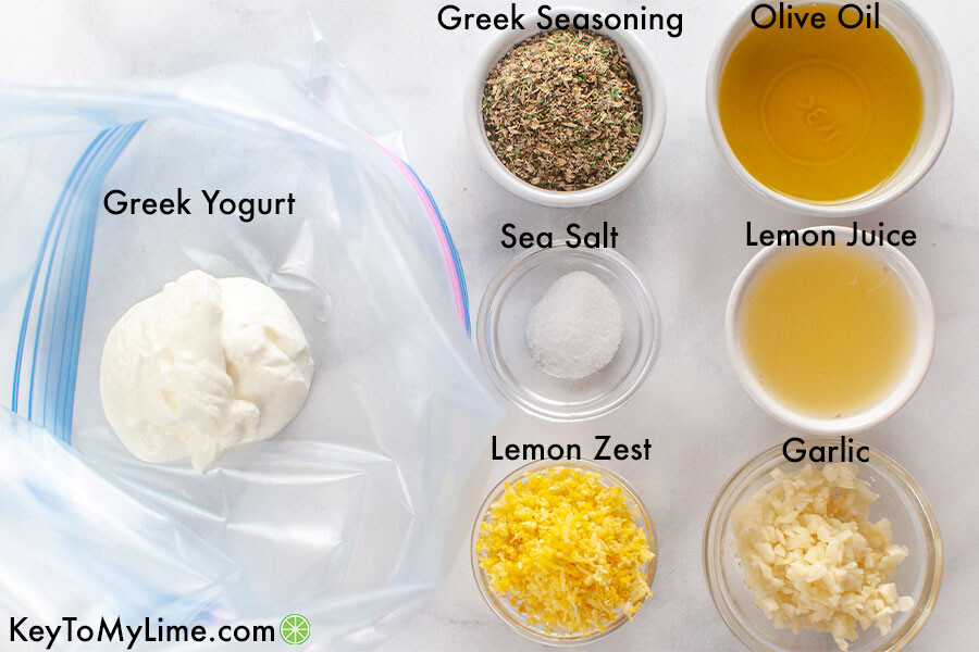 Greek chicken marinade ingredients in individual containers and labeled.