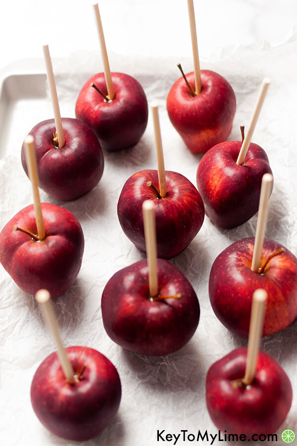 Red delicious apples with a stick in each ready to be dipped in chocolate.
