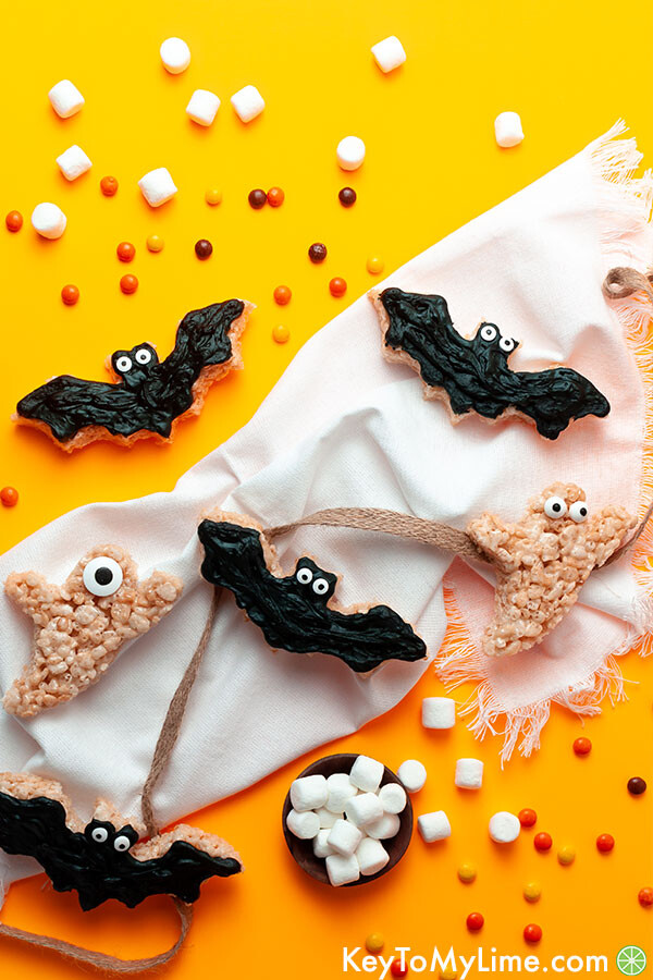 Bat and ghost rice krispie treats surrounded by candy on an orange background.