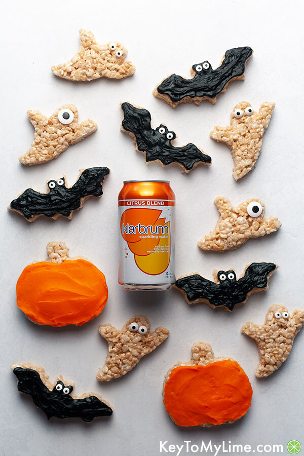 Bat, ghost, and pumpkin rice krispie treats surrounding a can of orange sparkling water.