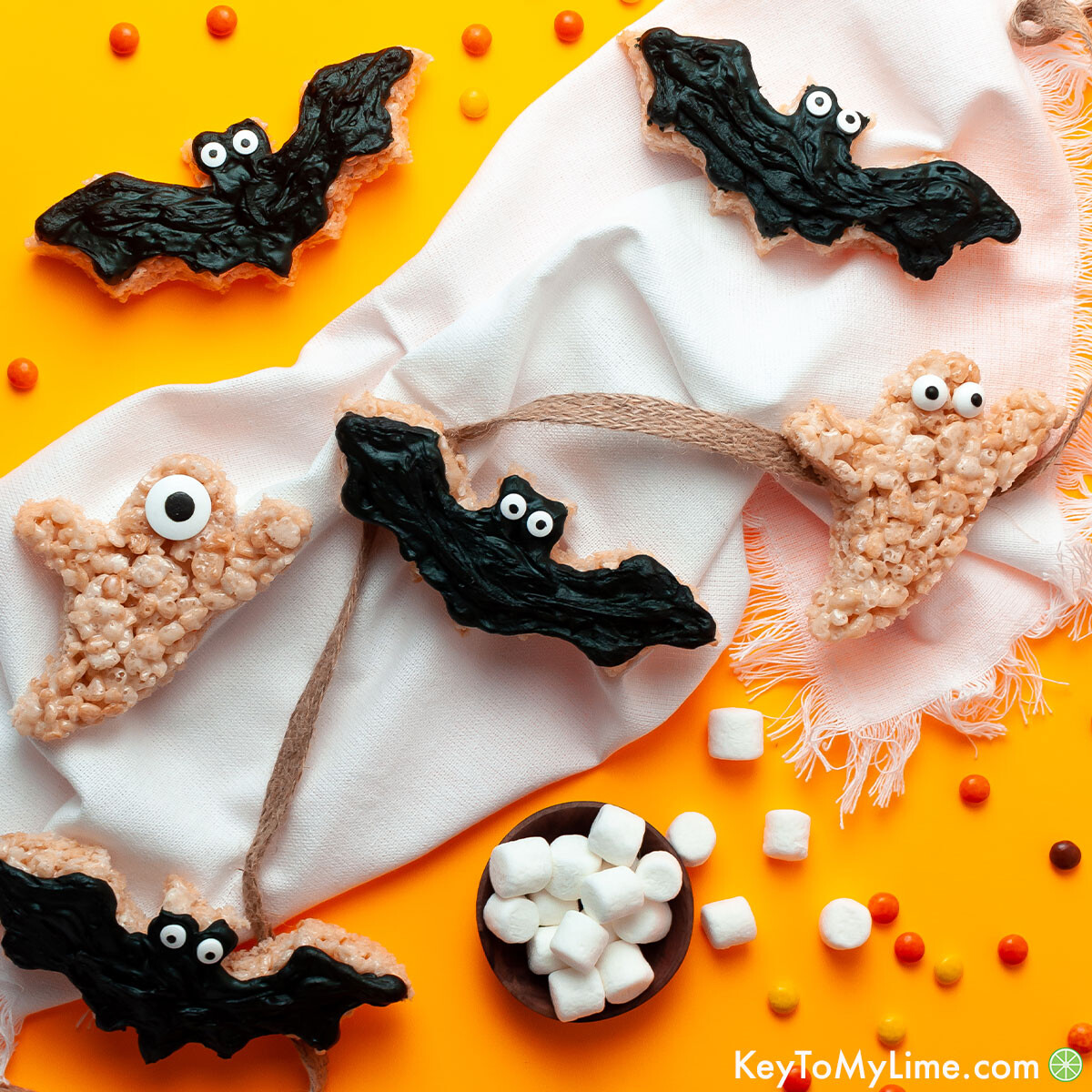Bat and ghost rice krispie treats on an orange background.