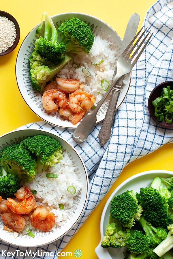 Two plates of honey garlic shrimp on a yellow background.