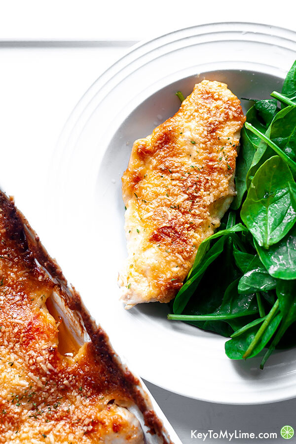 Melt in your mouth chicken served in a white bowl with spinach salad.