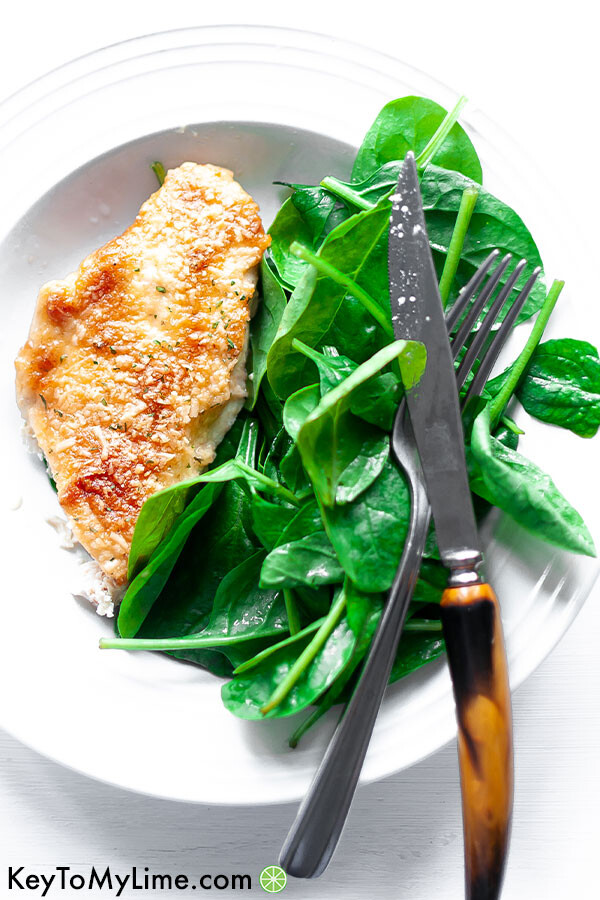 Melt in your mouth chicken on a plate next to spinach with a fork and knife.