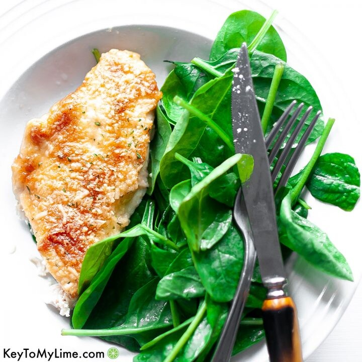 Melt in your mouth chicken on a plate next to spinach.