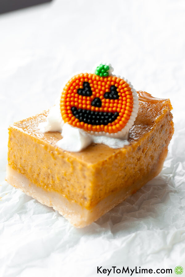 A single pumpkin pie bar on a white background topped with a candy pumpkin.