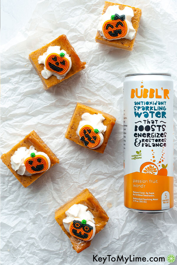 An overhead image of pumpkin bars next to a can of flavored sparkling water.