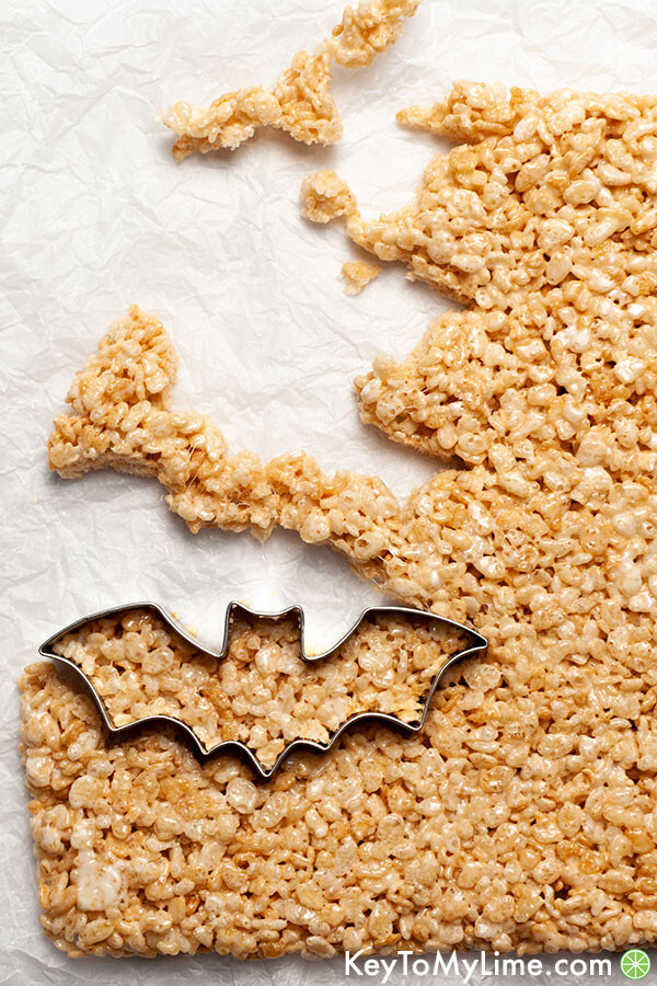 A cookie cutter cutting out shapes in rice krispie treats.