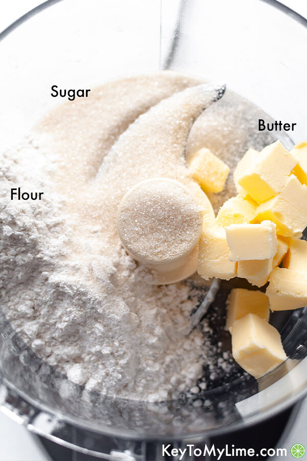A labeled ingredient image showing flour, butter, and sugar before blending in a food processor.