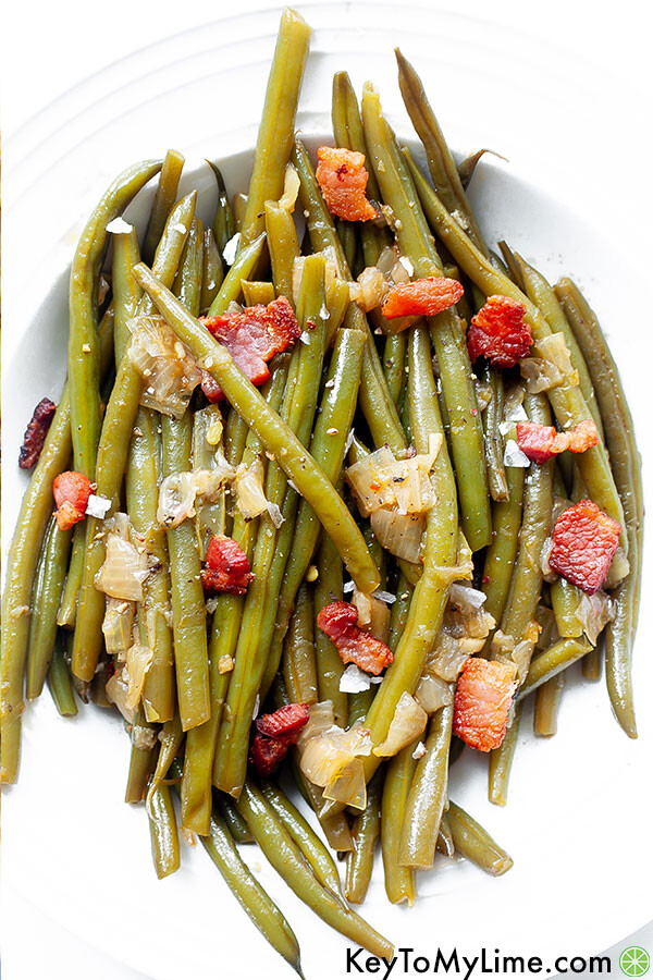 A bowl of Southern green beans on a white background.